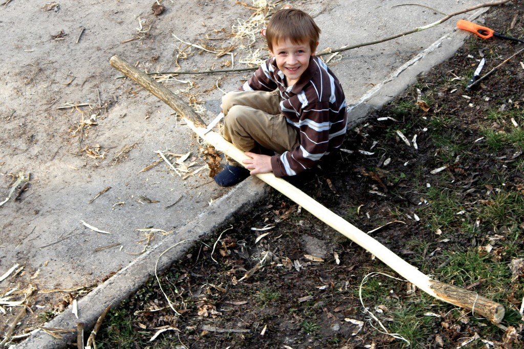 Noah whittling a branch into a spear (weapon of choice for hunger games).