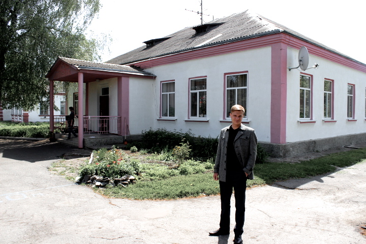 Dema standing outside the main Burty orphanage building.